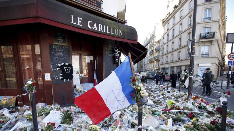 "A French flag flies over flowers, candles and messages in tribute to victims outside ""Le Carillon"" restaurant a week after a series of deadly attacks in the French capital Paris"