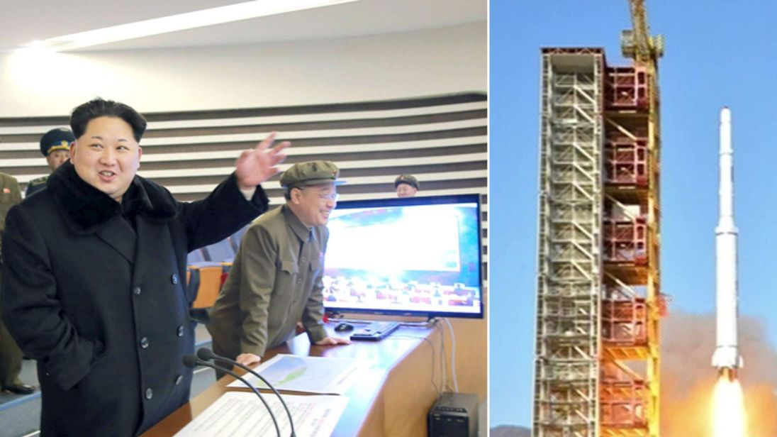 North Korean leader Kim Jong Un (C) reacts as he watches a long range rocket