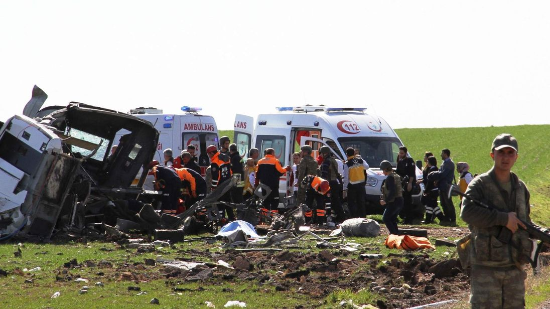 Members of emergency services work next to a damaged military vehicle near Diyarbakir