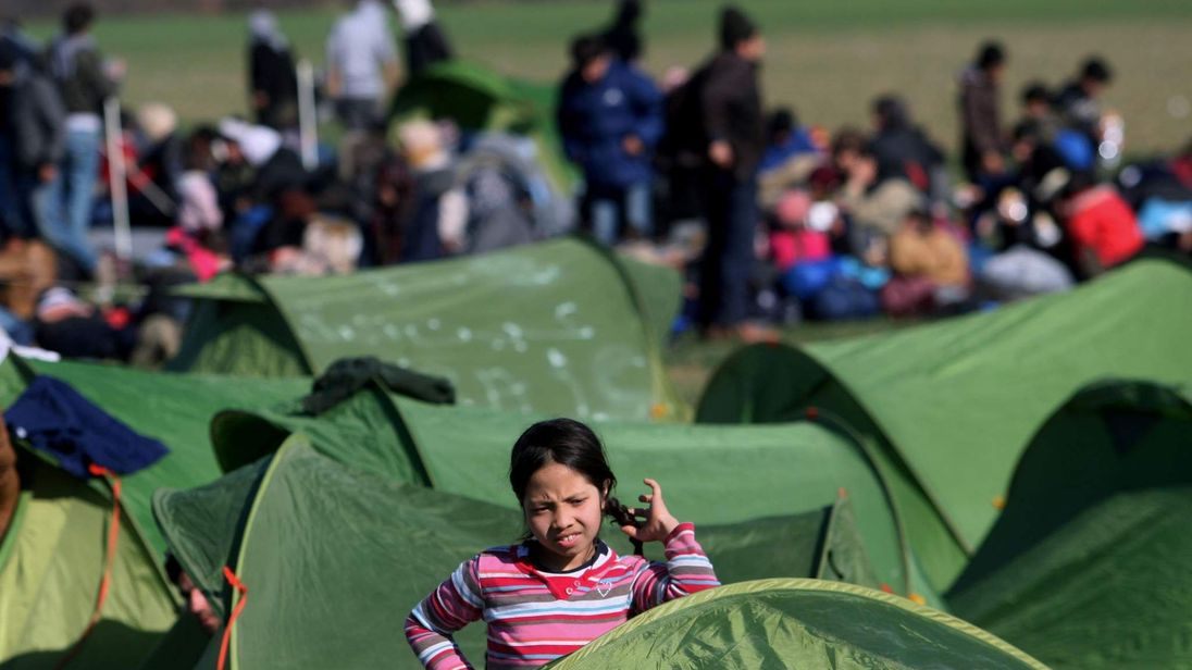 A girl migrant rests among tents in Greece