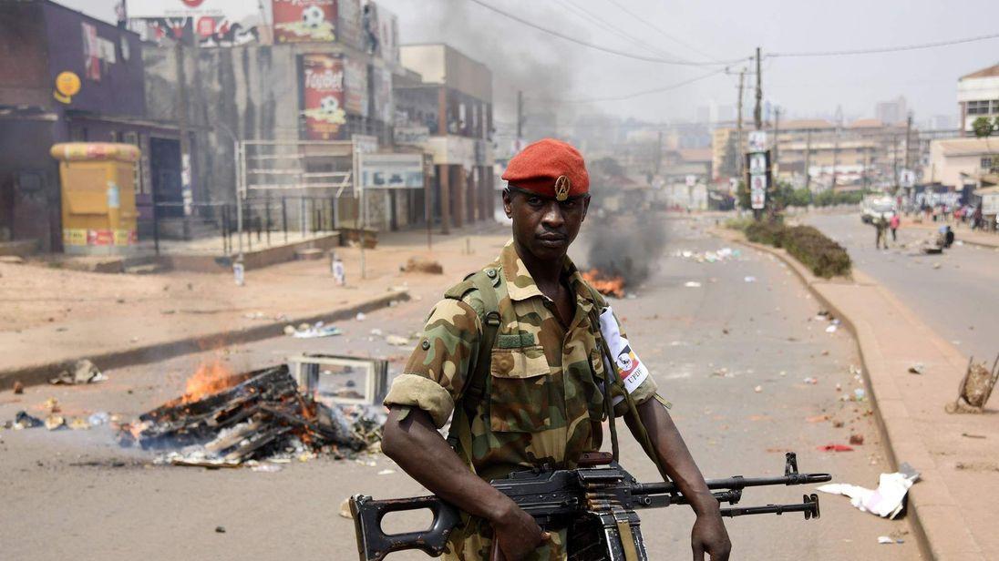 A Ugandan military police officer walks past a burning barricade across a street in Kampala