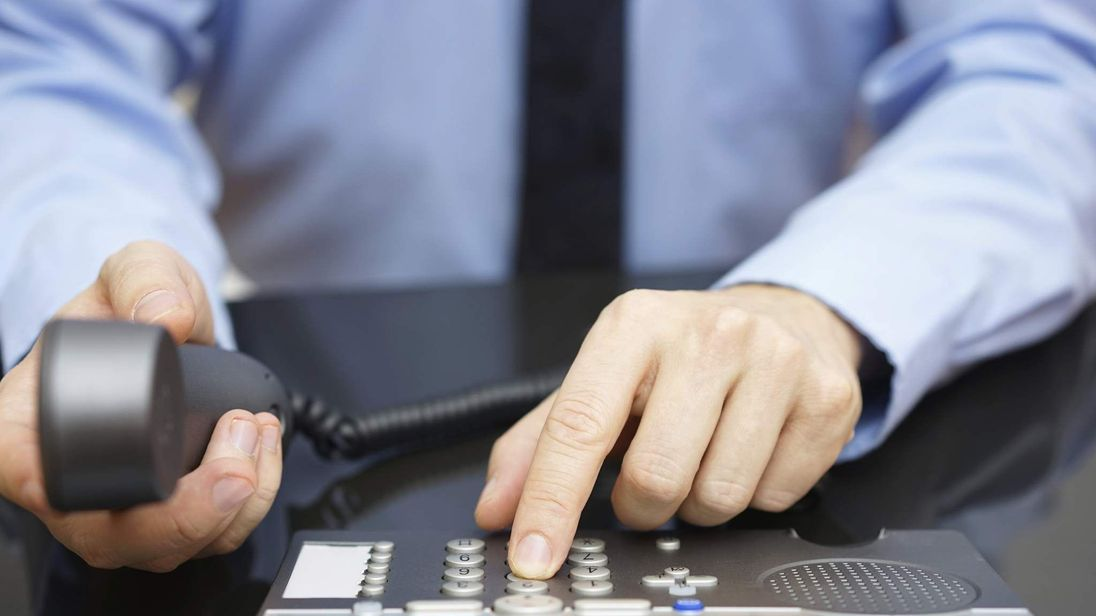 A caller dials a number on a phone