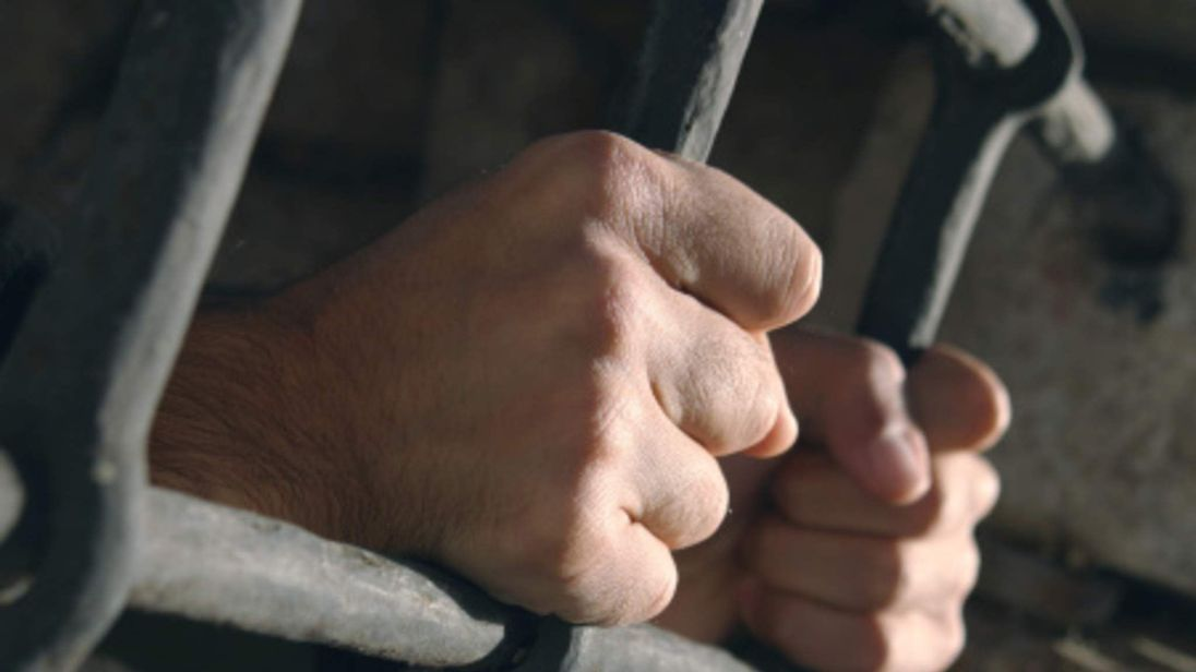 Hands Behind Bars In Prison Cell