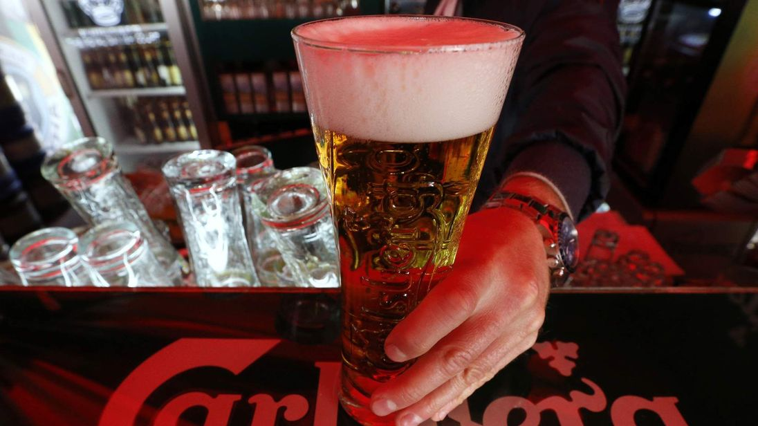 A bartender holds a glass of Carlsberg beer in a bar in St Petersburg, Russia