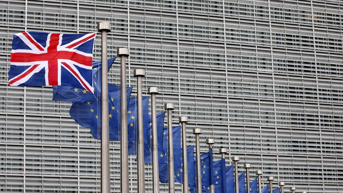 A Union Jack flag flutters next to European Union flags ahead of a visit from Britain's Prime Minister David Cameron at the EU Commission headquarters in Brussels