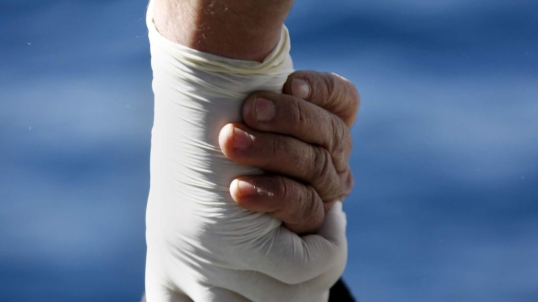 A migrant holds the hand of a Greek Coast Guard officer, while being retrieved from a dinghy carrying refugees and migrants aboard the Ayios Efstratios Coast Guard vessel, during a rescue operation at open sea