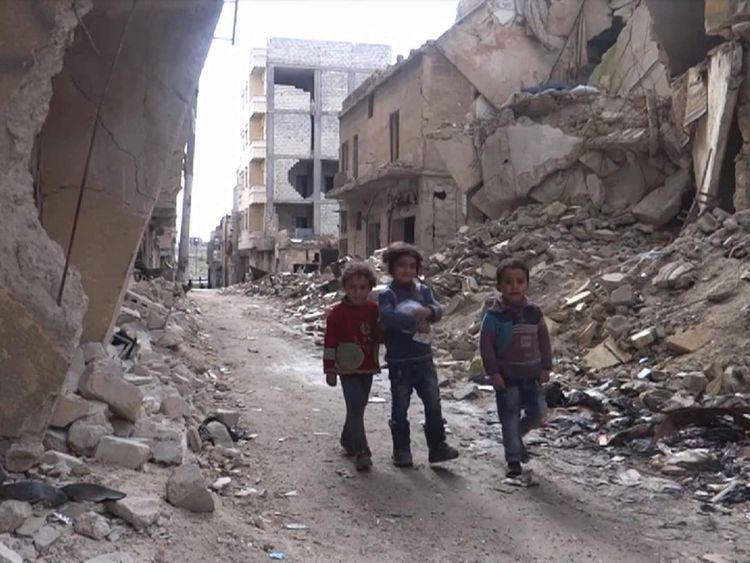 Children walk through rubble in Aleppo