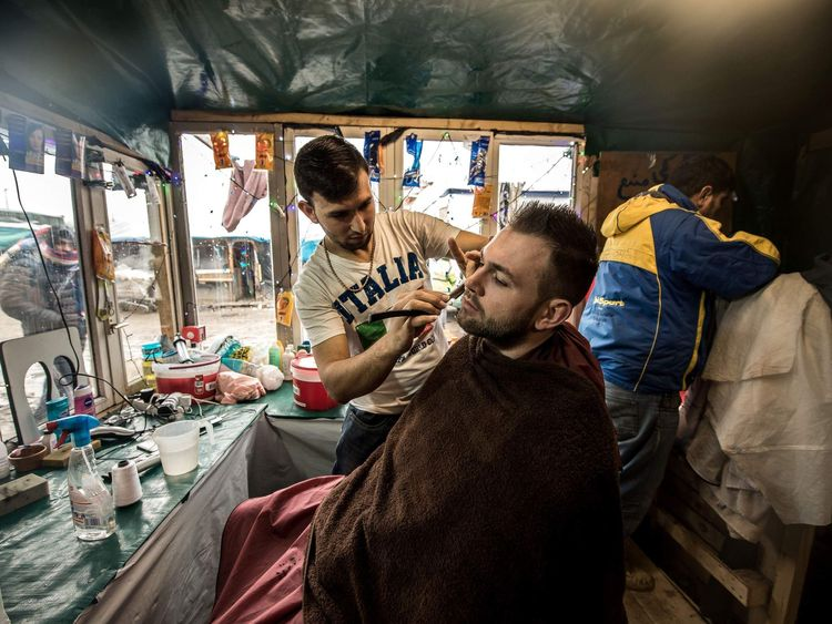 A migrant shaves another in his makeshift hairdressing salon