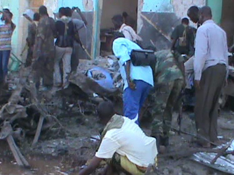 People and soldiers search in the rubble of a destroyed building in Baidoa after twin explosions in the Somali city killed at least 30