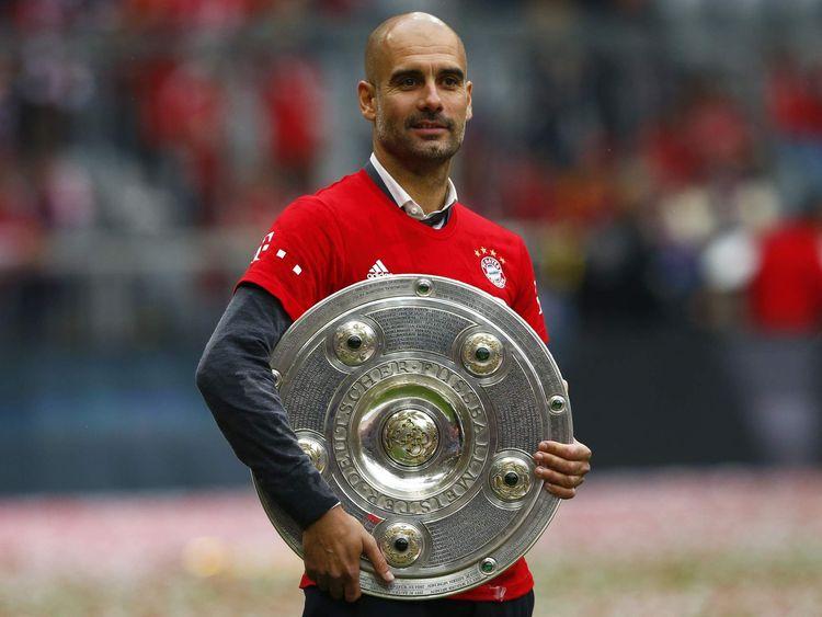 Bayern Munich's coach Pep Guardiola holds the Bundesliga trophy.