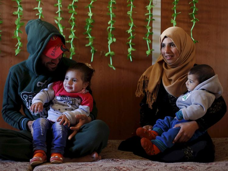 Syrian refugee Burooq Al Zubi carries her son Fares while posing with her husband Osama, who is carrying their daughter Khitam at Al Zaatari refugee camp in the Jordanian city of Mafraq, near the border with Syria