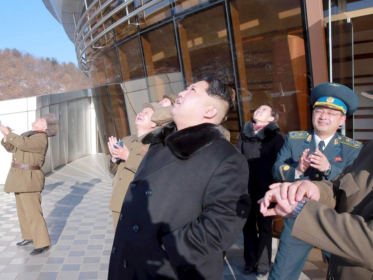 North Korean leader Kim Jong Un (C) watches a long range rocket launch into the air in North Korea