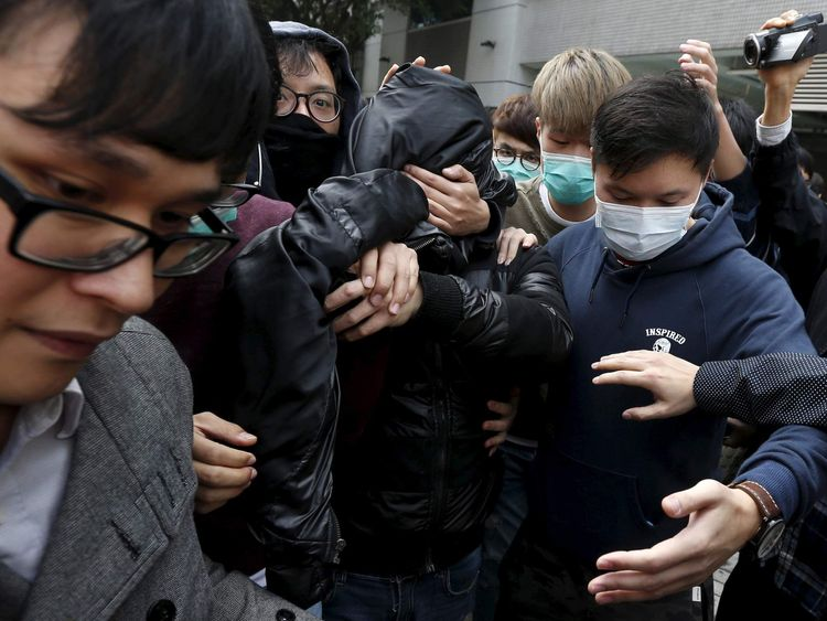 A suspect is covered by a jacket with supporters surrounding him as he leaves to go on bail at a court in Hong Kong