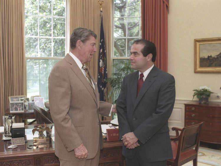 File photo of U.S. President Ronald Reagan speaking with Supreme Court Justice nominee Antonin Scalia in the White House Oval Office
