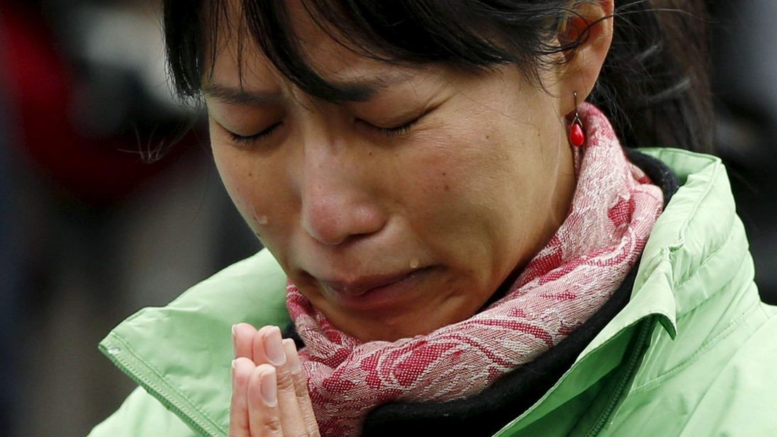 A participant observes a moment of silence in Tokyo on the fifth anniversary of the March 11, 2011 earthquake and tsunami
