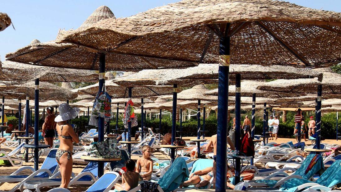 Tourists sunbathe on the sea side at the Red Sea resort of Sharm el Sheikh