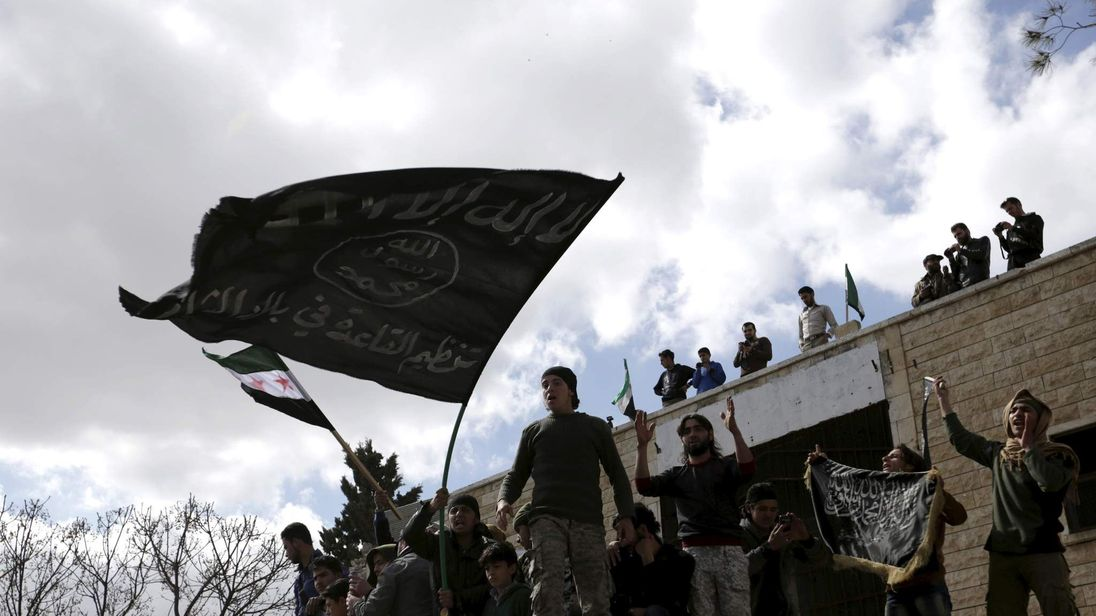 Protesters carry Al-Qaeda flags during an anti-government protest after Friday prayers in the town of Marat Numan in Idlib province