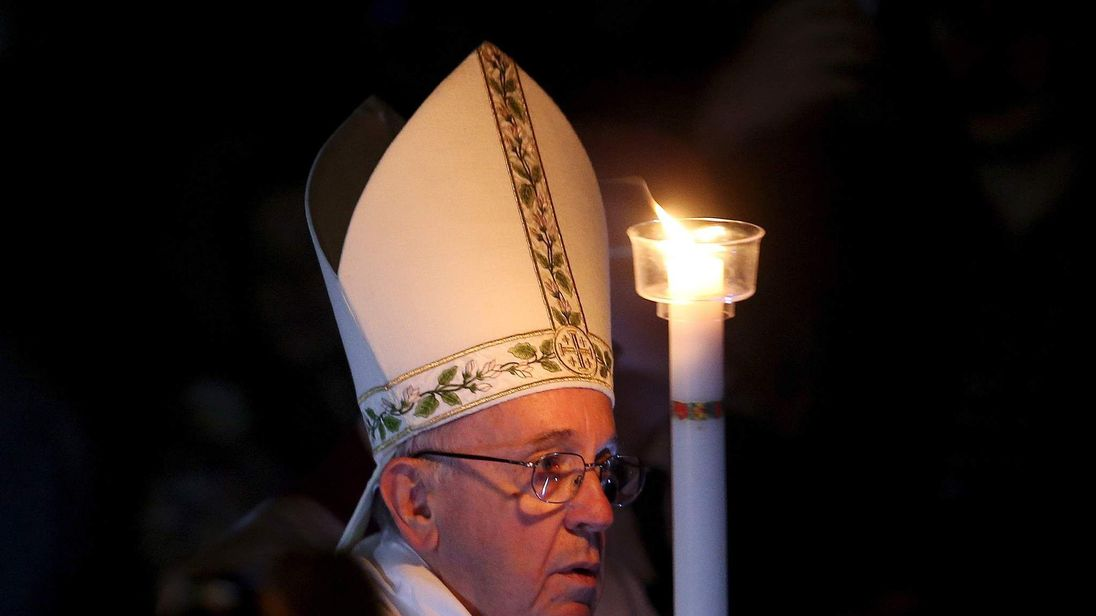 Pope Francis holds a candle as he arrives to leads the Easter vigil