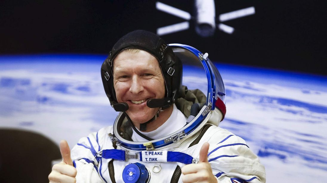 Crew member Timothy Peake of Britain gestures after donning a space suit at the Baikonur cosmodrome, Kazakhstan
