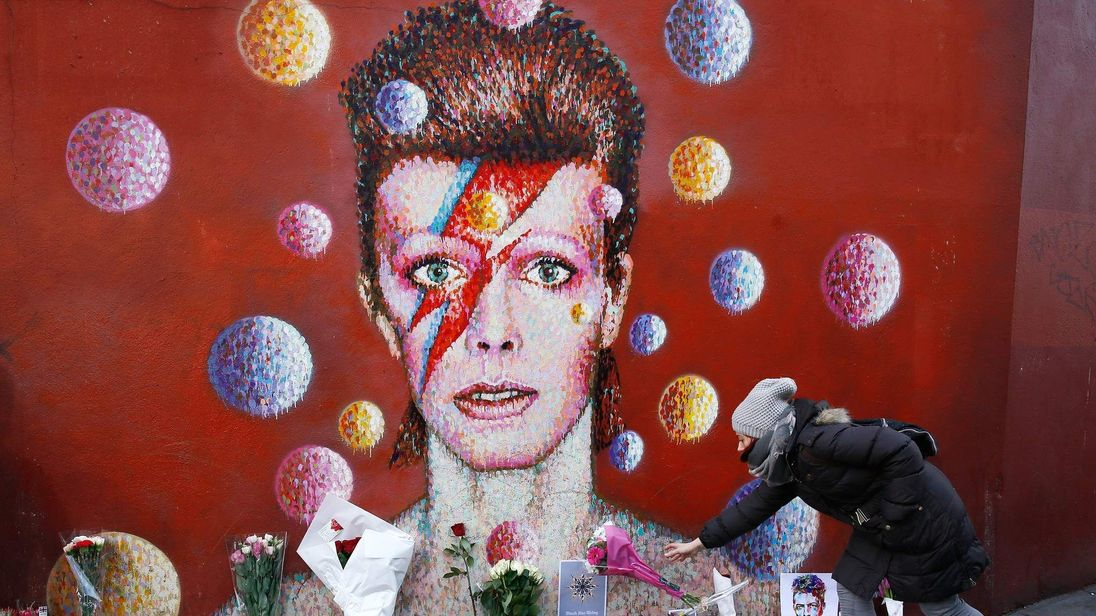 A woman leaves a bouquet at a mural of David Bowie in Brixton, south London