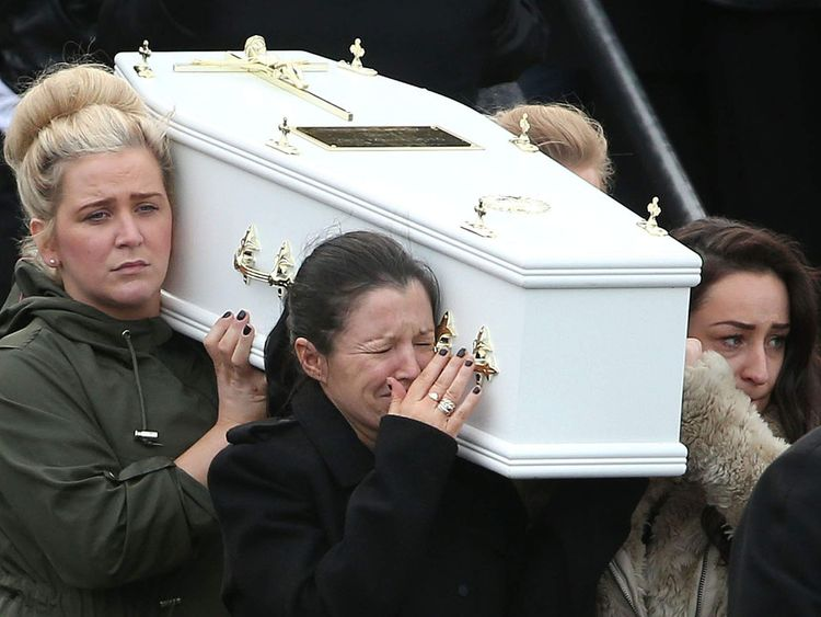 Louise James, front left, carries a coffin out of the Holy Family church