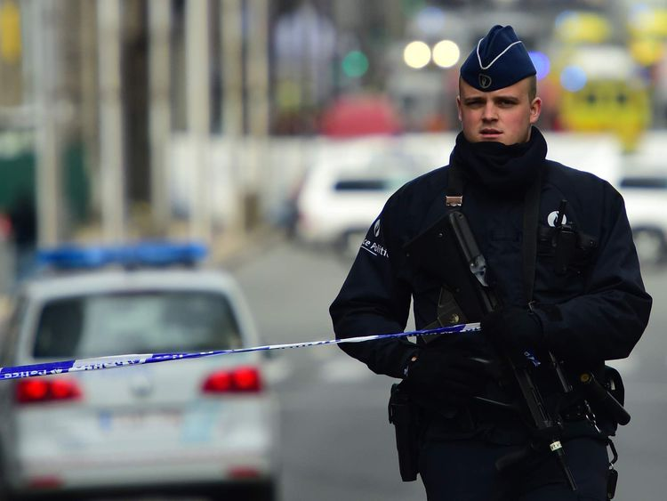 A police officers sets a security perimeter near Maalbeek metro station in Brussels.
