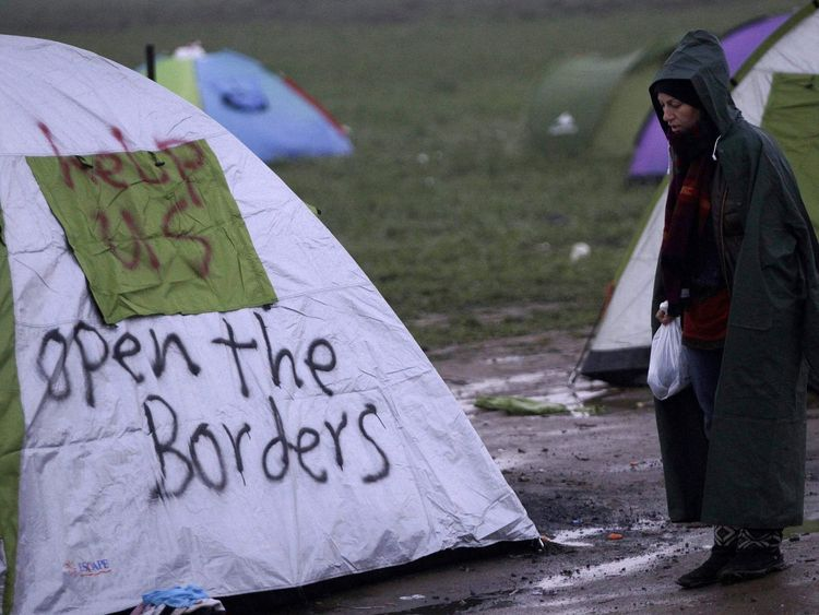 A refugee stands next to a tent at a relocation camp where stranded refugees and migrants wait to cross the Greek-Macedonian border, near the Greek village of Idomeni