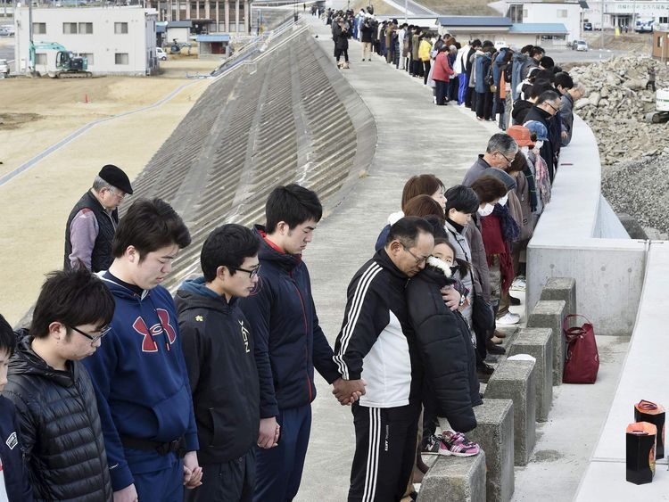 People observe a moment of silence at 2:46 p.m., the time when the magnitude 9.0 earthquake struck off Japan's coast in 2011, atop of a seawall at Taro district in Miyako, Iwate prefecture, Japan
