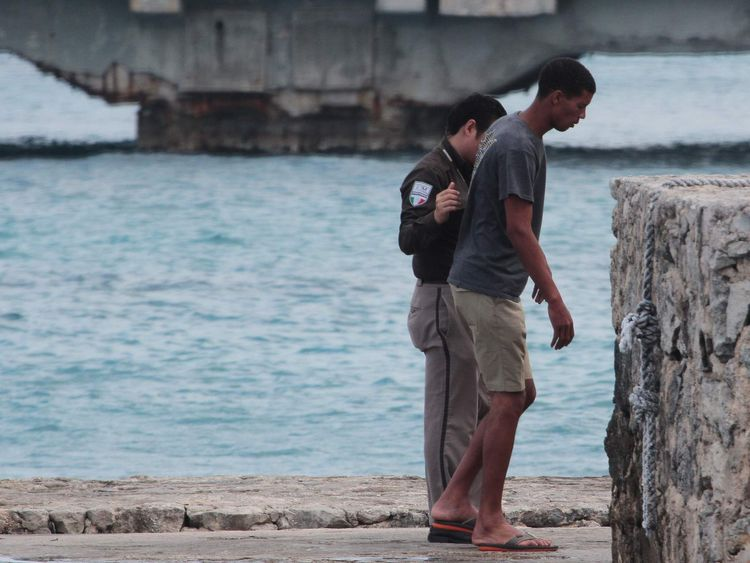 A Cuban migrant is being helped by a Mexican immigration officer, after he and fellow Cuban migrants were picked up by a cruise ship off the Florida coast, in Cozumel