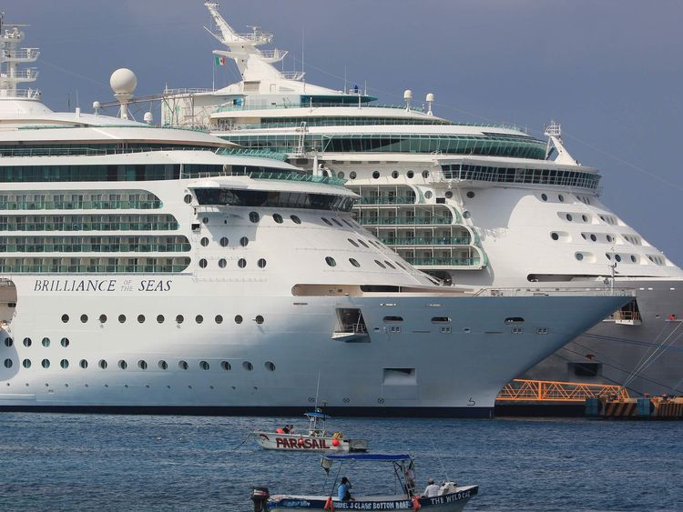 The Royal Caribbean's Brilliance of the Seas cruise ship (L) is pictured after it had picked up several Cuban migrants off the Florida coast on Friday, handing them over to Mexican immigration officers on Saturday in Cozumel
