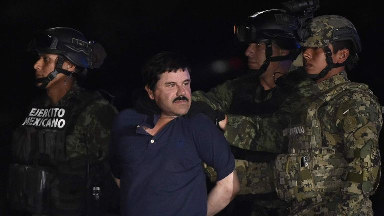 "Drug kingpin Joaquin ""El Chapo"" Guzman is escorted by marines to a helicopter at Mexico City's airport on January 8"