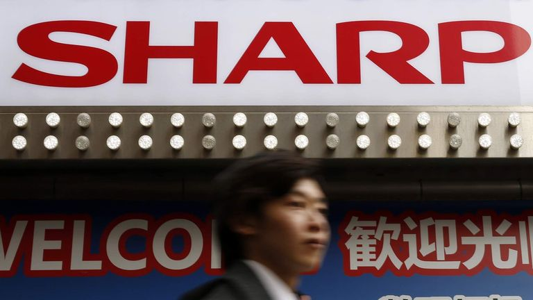 A logo of Sharp Corp is seen above a Chinese tourist standing outside an electronics retail store in Tokyo
