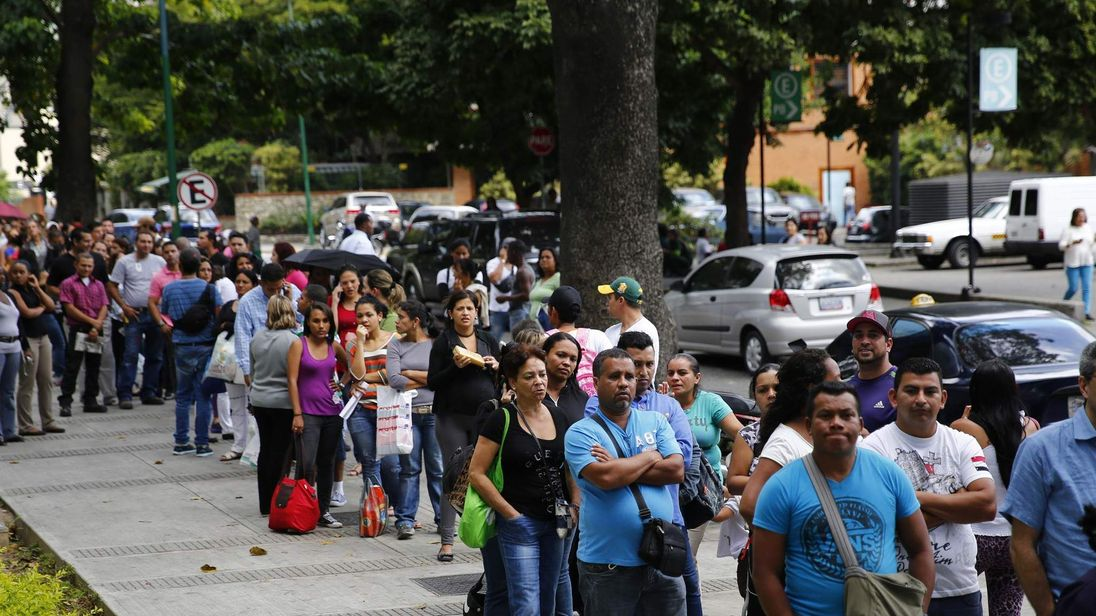 People line up outside a pharmacy to buy baby diapers in Caracas
