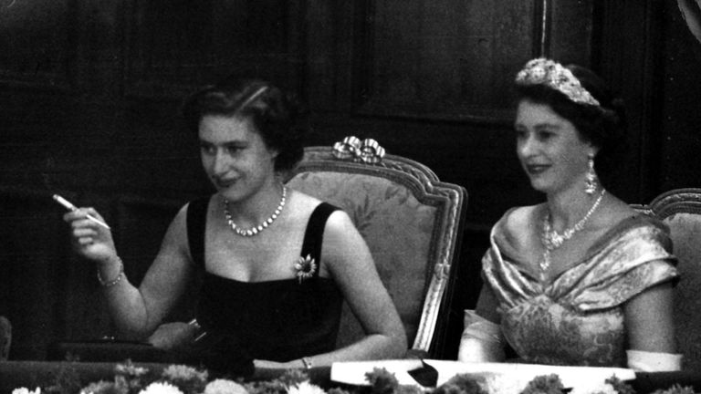 Queen Elizabeth II, right, and her sister, Princess Margaret, smoking a cigarette, watch the Royal Variety Performance