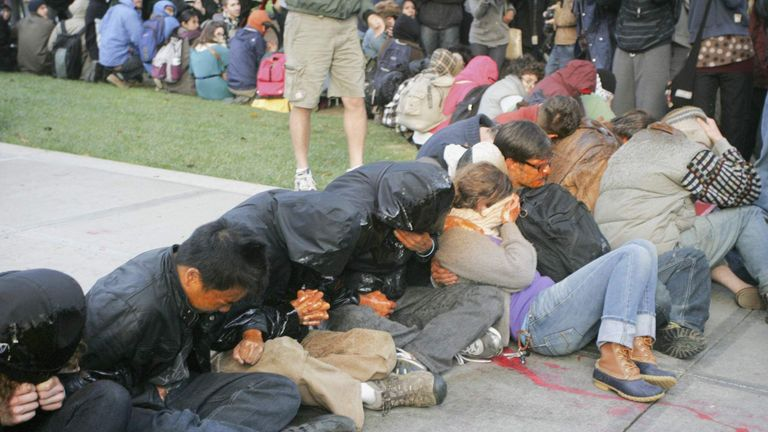 "University of California Davis students covered in pepper spray sit during an ""Occupy UCD"" demonstration in Davis"