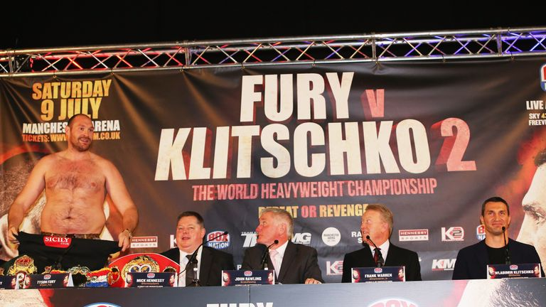 Tyson Fury (L) removed his shirt during the press conference