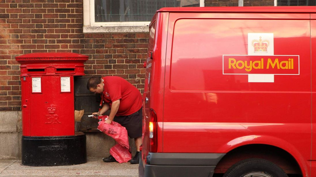 A postman empties a postbox