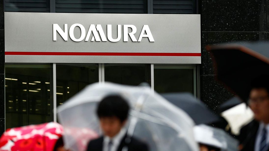 People walk past a branch of the Nomura financial services group in Tokyo