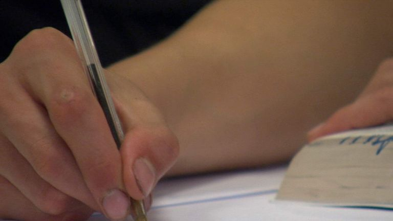 A student writing during a school lesson