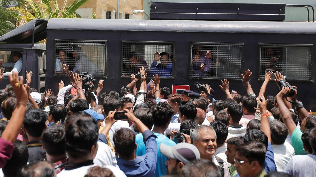 A police van transports some of those convicted in connection with a riot in Gujarat in 2002, outside a court after the ruling in Ahmedabad