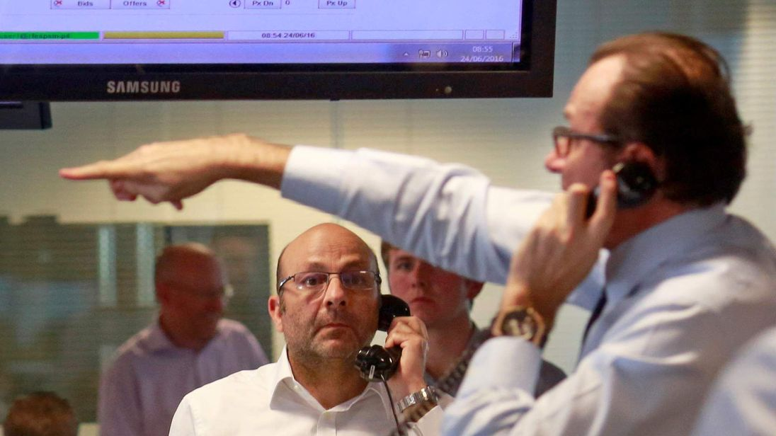 Traders from BGC, a global brokerage company in London's Canary Wharf financial centre react during trading