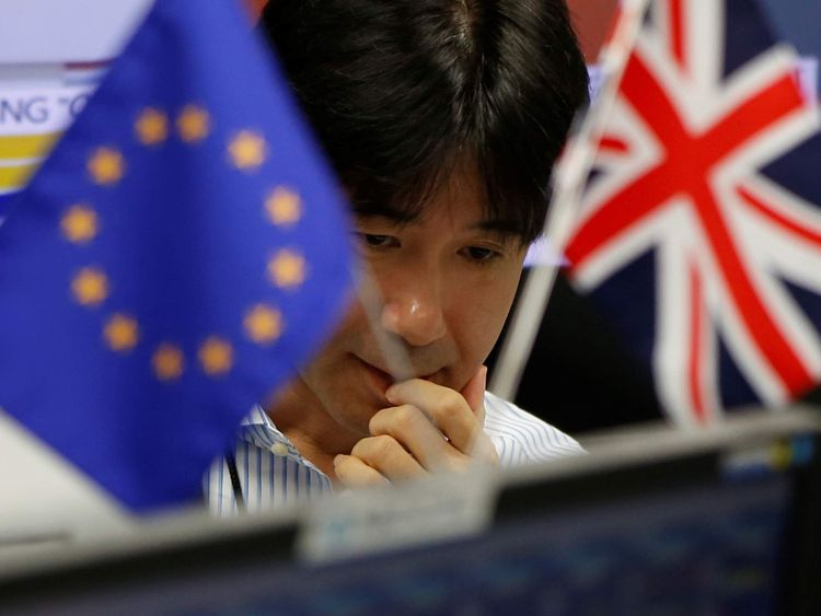 An employees of a foreign exchange trading company works as he is seen between British Union flag and an EU flag in Tokyo