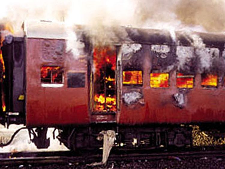 Smoke pours from the carriage of a train on fire in Godhra, in the western Indian state of Gujarat, ..