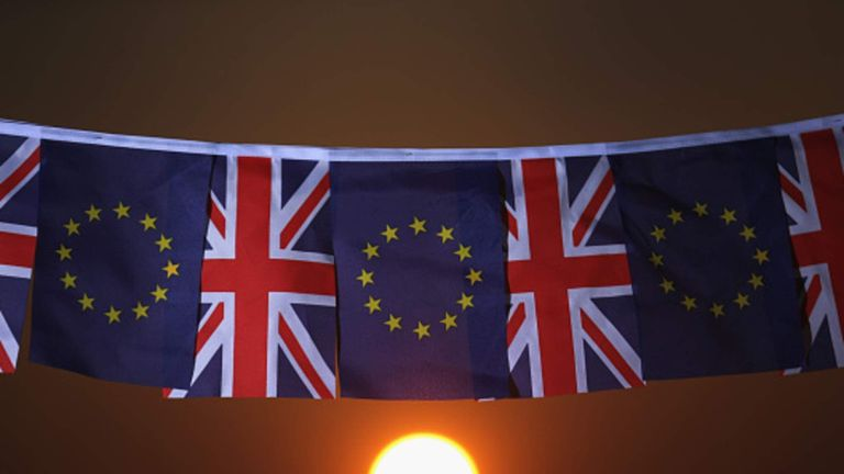 The sun sets behind the EU and the UK flags