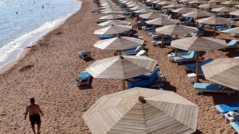 A tourist walks past sunbeds on a beach in Egypt's Red Sea resort of Sharm El-Sheikh
