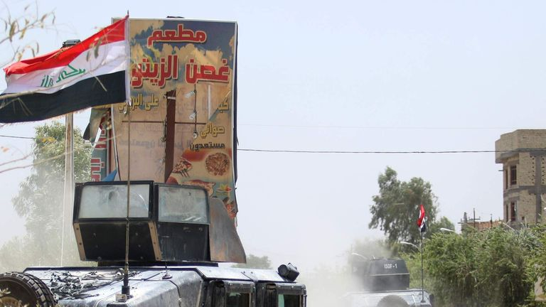 Iraqi counter-terrorism forces drive armed vehicles flying their national flag in Fallujah
