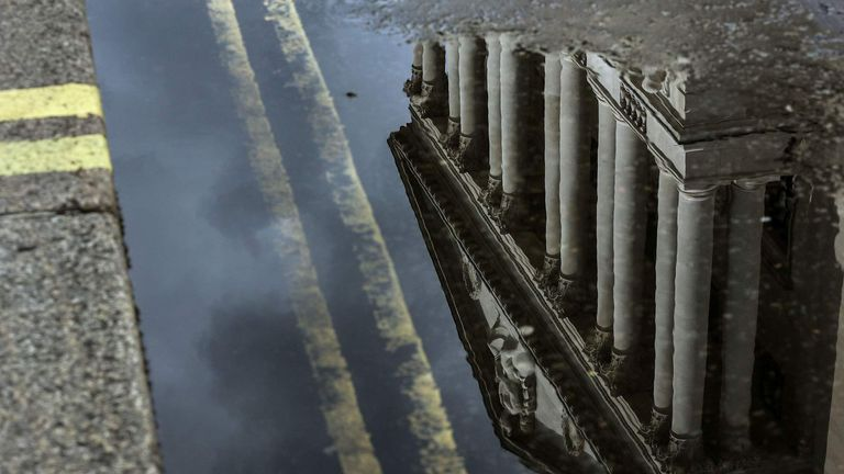 The Bank of England is reflected in puddle of rain water in the City of London