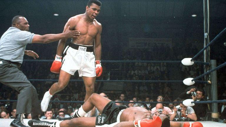 Muhammad Ali is held back by referee Joe Walcott, left, after Ali knocked out challenger Sonny Liston