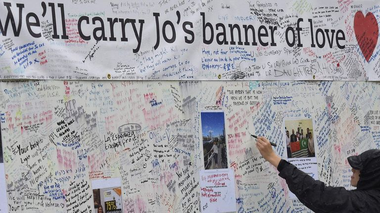 A man writes a tribute on a message board erected in memory of murdered Labour Party MP Jo Cox, who was shot dead in Birstall, at Parliament Square in London