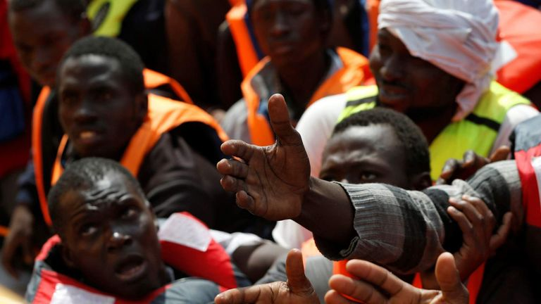 Migrants in a dinghy reach out towards Migrant Offshore Aid Station rescuers on board of the MOAS ship Topaz Responder around 20 nautical miles off the coast of Libya